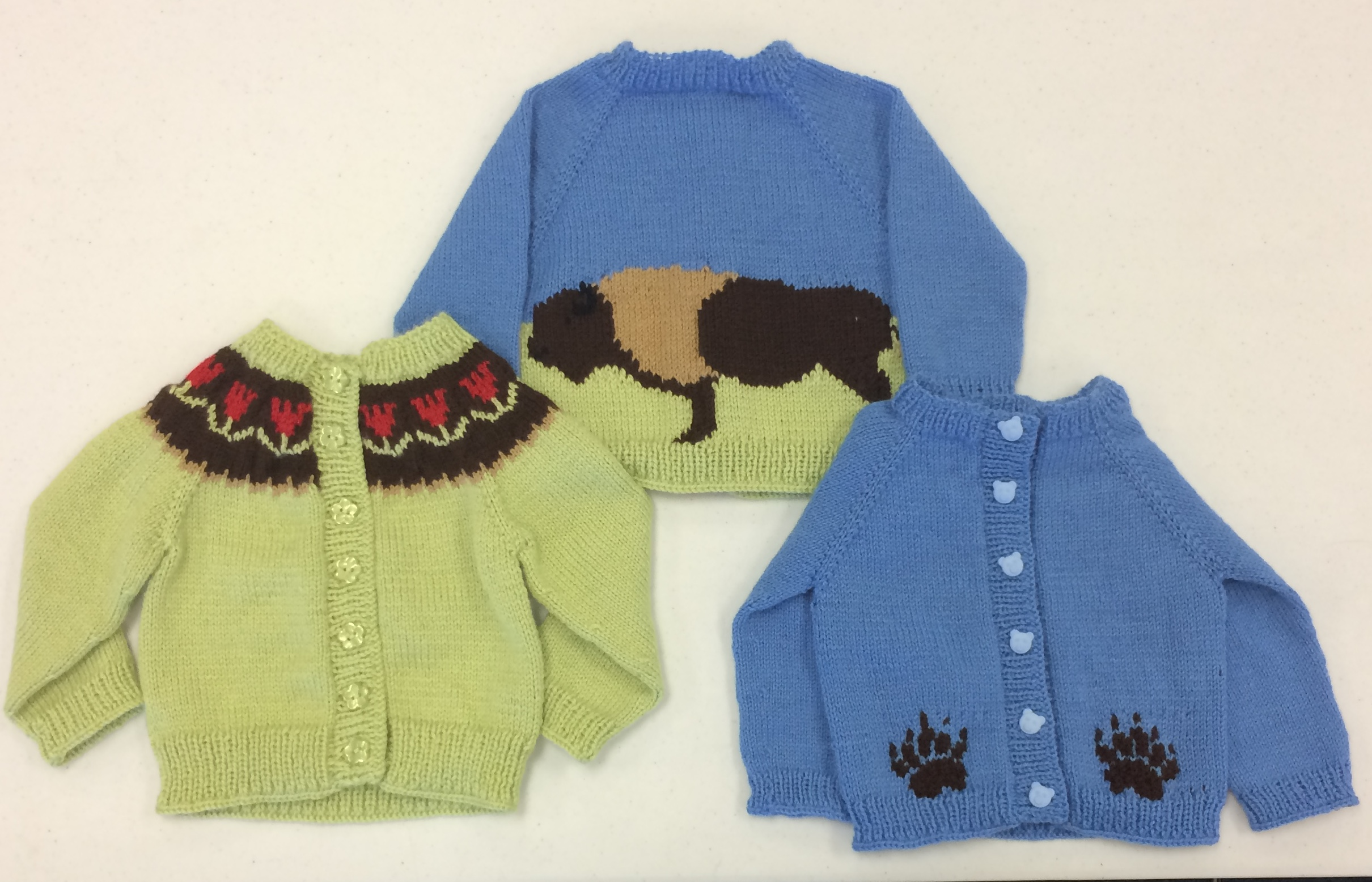 Three baby sweaters